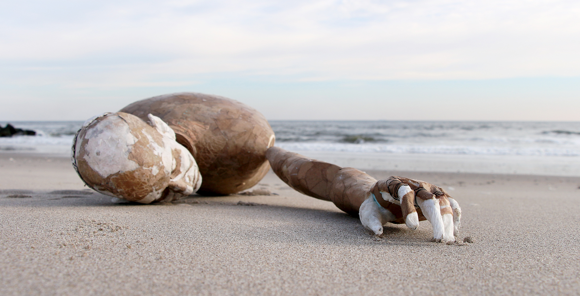 A brown puppet is lying face down on a beach with one hand outstretched toward the camera