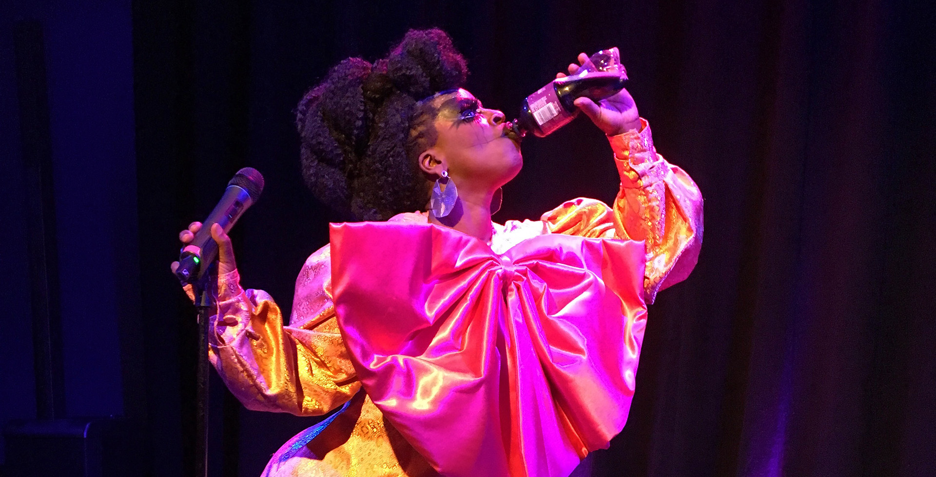 Drag Queen Black Benatar holds a mike in one hand and drinks a bottle of Dr Pepper with the other, in a sequined gold and pink dress with a giant pink bow