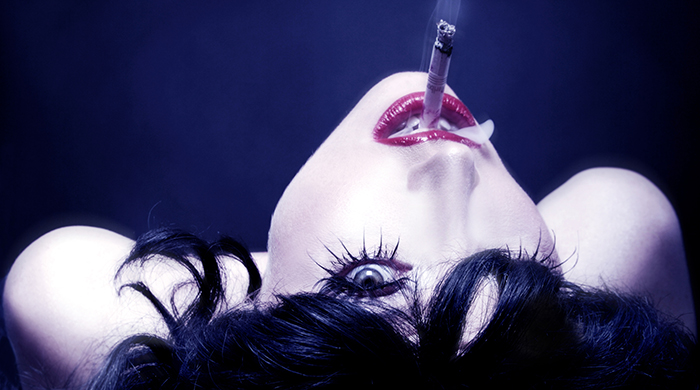 A white woman with black hair, with red lipstick and a cigarette, is looking backwards and upside down at the camera