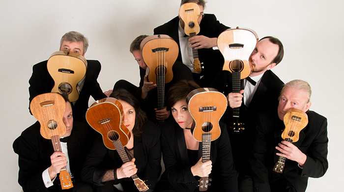 Eight musicians holding ukuleles in front of their faces