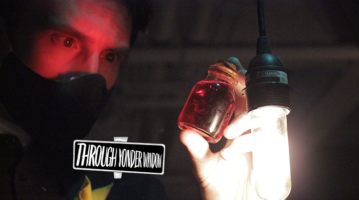 A man wearing a mask, illuminated by a single light bulb, looking at a vial of red liquid